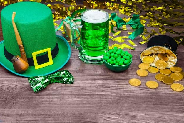 Día de san patricio. sombrero verde de duende con pinta verde de cerveza, monedas de oro, pipa de fumar y dulces verdes en mesa de madera Foto Premium