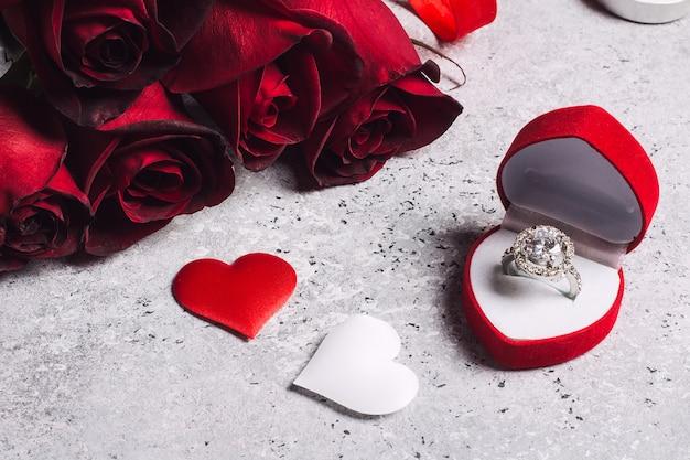Día de san valentín cásate conmigo en la caja del anillo de compromiso de boda con un regalo de rosa roja Foto gratis