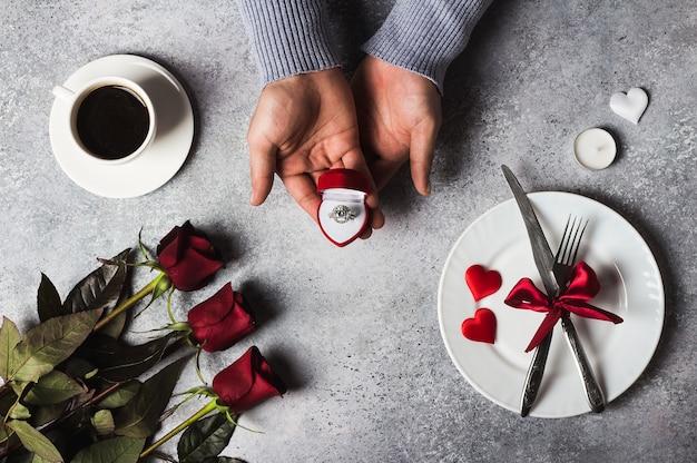 Día de san valentín cena romántica mesa ajuste hombre mano sosteniendo el anillo de compromiso Foto gratis