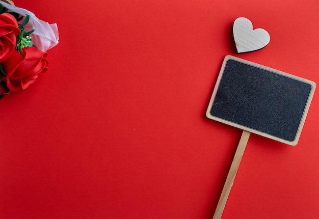 Día de san valentín corazón de madera sobre fondo rojo Foto Premium