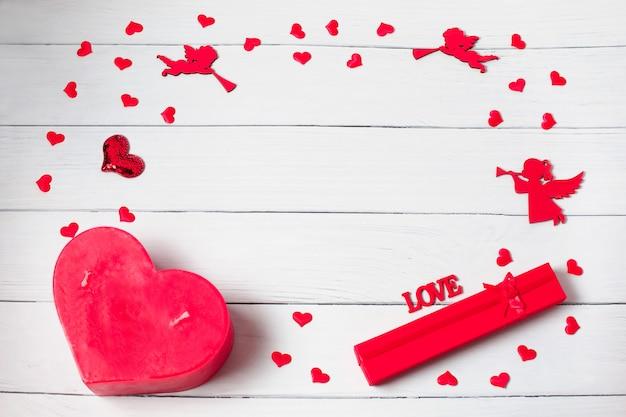 Día de san valentín. marco hecho de regalos, velas, confeti, ángeles sobre fondo de madera. fondo del día de san valentín Foto Premium