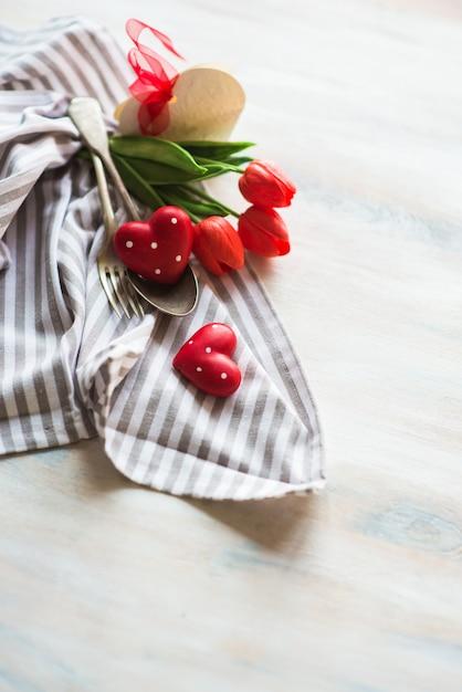 Día de san valentín con mesa, flores y corazones. Foto Premium