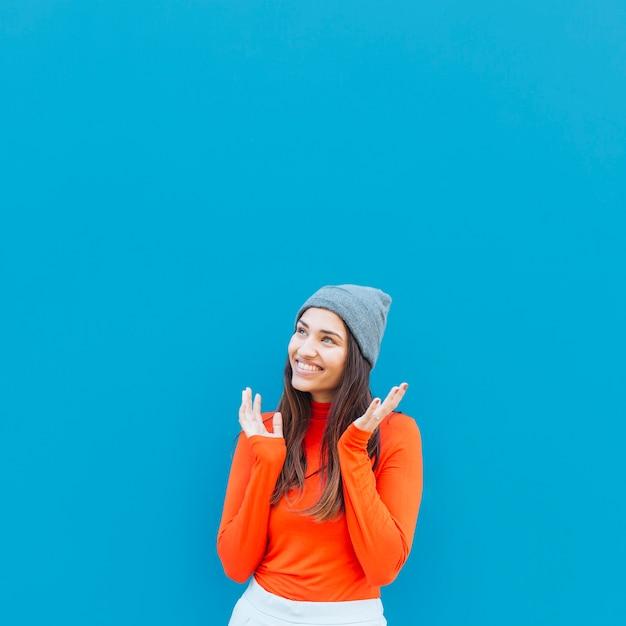 Día sonriente que sueña a la mujer que mira lejos contra fondo azul Foto gratis