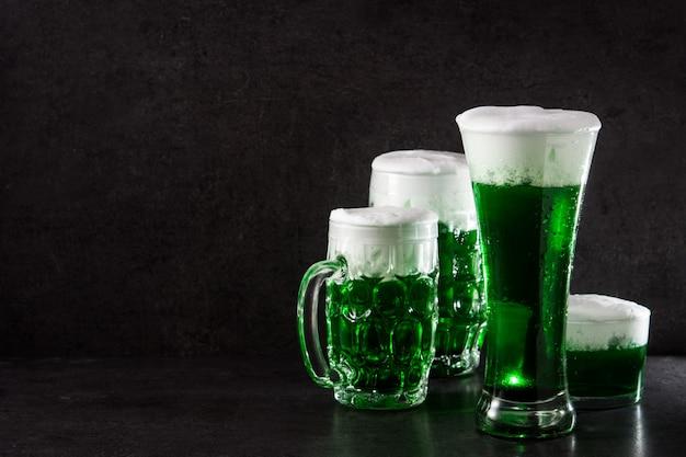 Día tradicional de san patricio cervezas verdes sobre fondo negro copia espacio Foto Premium