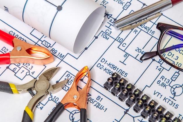 Diagramas eléctricos y pinzas metálicas que construyen un concepto de casa para proyectos de ingeniería. Foto Premium