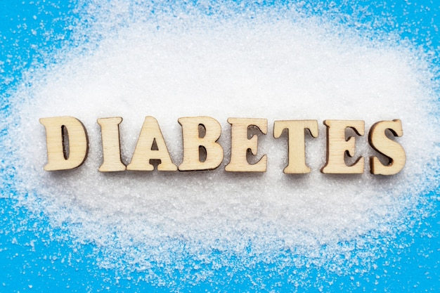 Diapositiva de azúcar e inscripción de diabetes en azul, vista superior Foto Premium