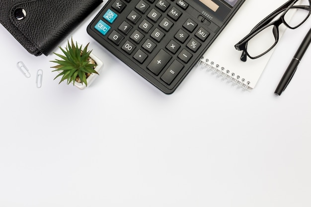 Diario, calcula, planta de cactus, cuaderno de espiral, lentes y bolígrafo sobre fondo blanco Foto gratis