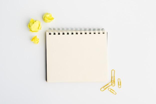 Diario espiral en blanco con papel arrugado amarillo y clip sobre fondo blanco. Foto gratis