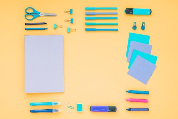 Diario; lápices de color; tijera con papelería de oficina dispuesta sobre fondo naranja Foto gratis