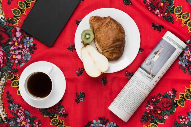Diario; taza de café; fruta; croissant y periódico sobre mantel floral rojo Foto gratis