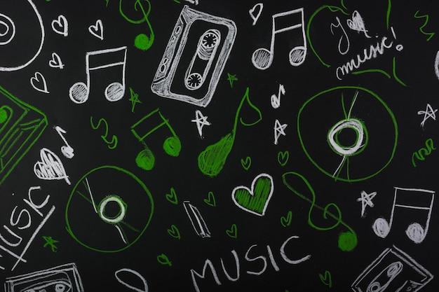 Dibujado notas musicales con cinta de cassette; disco compacto en pizarra Foto gratis