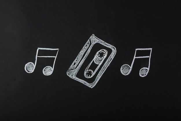Dibujado notas musicales con cinta de cassette en pizarra Foto gratis