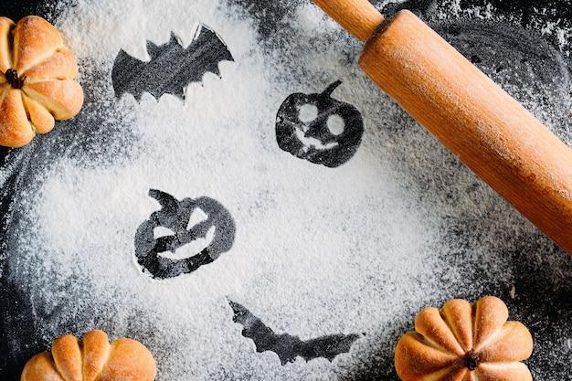 Dibujo de calabaza de halloween cabeza linterna y murciélago sobre fondo de harina de trigo Foto Premium