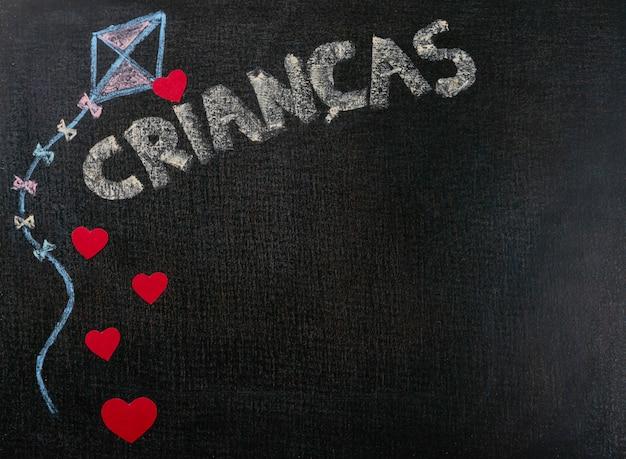 Dibujo sobre papel de lija. crianças (portugués) escrito en pizarra y corazones. copia espacio de fondo. Foto Premium