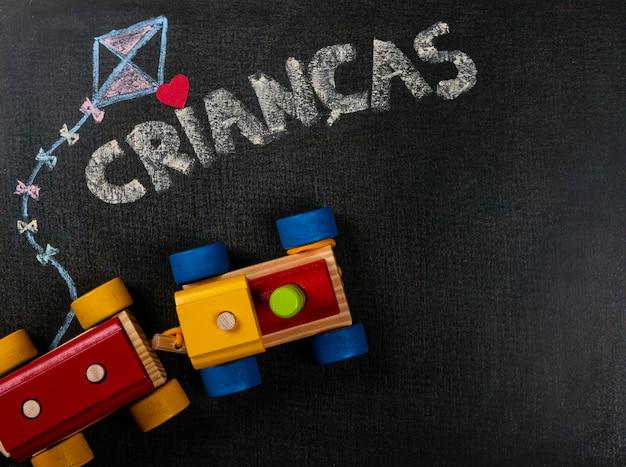 Dibujo sobre papel de lija. crianças (portugués) escrito en pizarra y ensamblando piezas. copia espacio Foto Premium