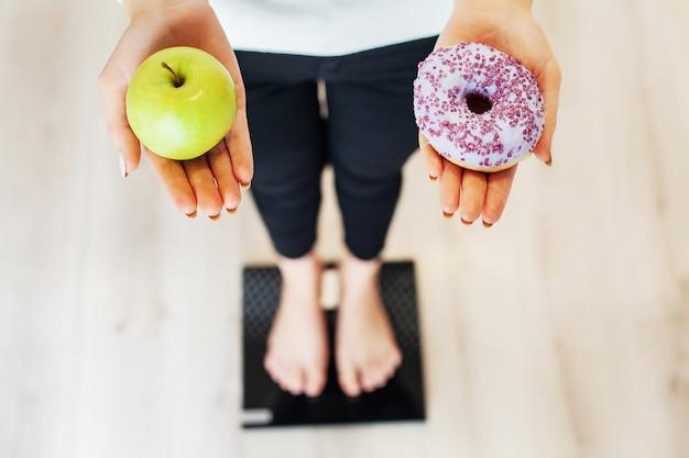 Dieta. mujer que mide el peso corporal en la balanza holding donut y manzana. los dulces son comida chatarra poco saludable. comida rápida Foto Premium