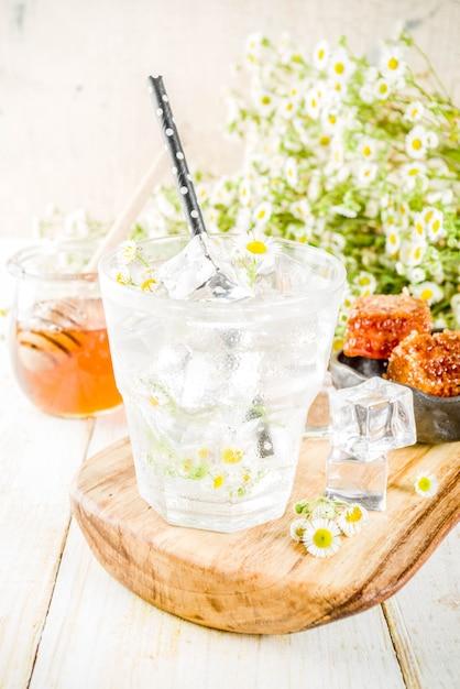 Dieta orgánica detox bebida de verano, bebida de agua infundida con manzanilla y miel, en mesa de madera blanca, con flores de manzanilla y miel en un frasco. copia espacio Foto Premium