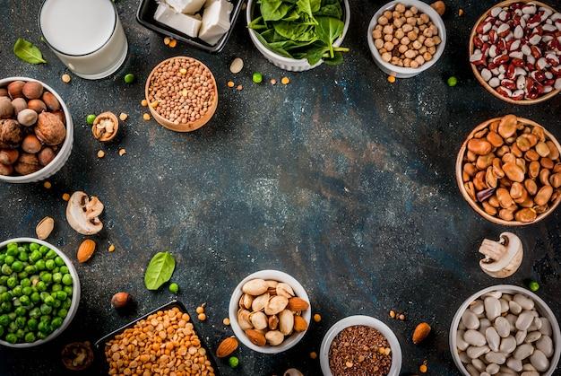 Dieta saludable comida vegana, fuentes de proteínas vegetales: tofu, leche vegana, frijoles, lentejas, nueces, leche de soja, espinacas y semillas. vista superior de la mesa blanca. Foto Premium