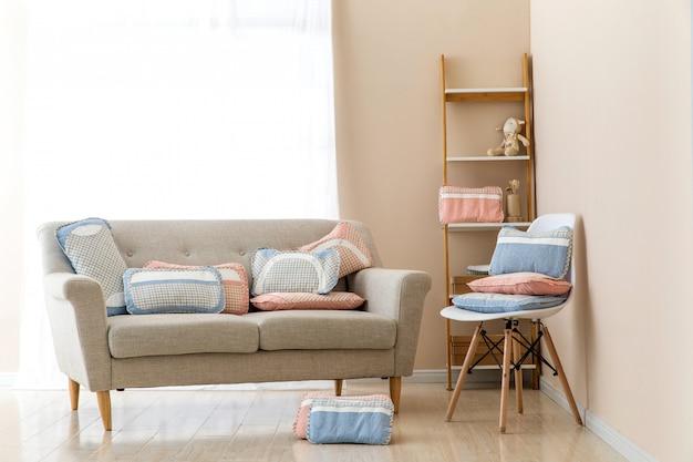 Diferentes almohadas en silla en habitación Foto Premium