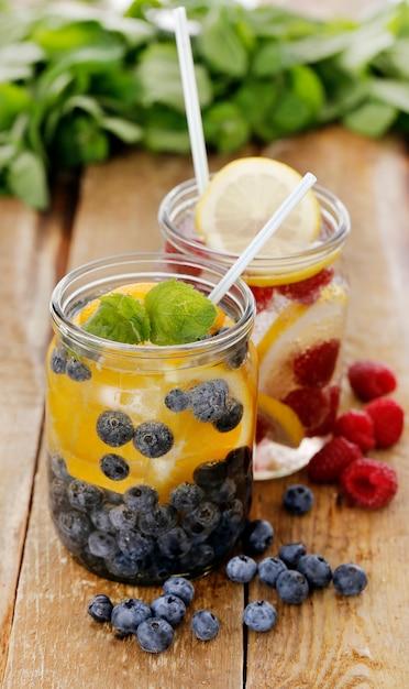 Diferentes bebidas frías con pajitas en una mesa de madera Foto gratis