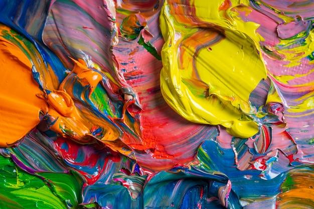 Diferentes colores brillantes de pinturas al óleo se mezclan en un primer plano de la paleta. Foto Premium