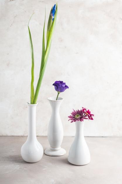 Diferentes flores colocadas en jarrones blancos. Foto gratis
