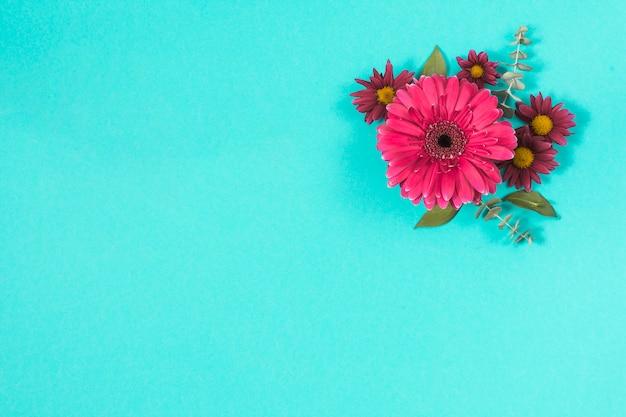 Diferentes flores con hojas en mesa. Foto gratis