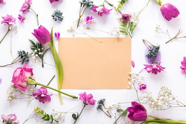 Diferentes flores con papel en blanco sobre mesa. Foto gratis