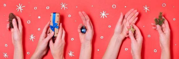 Diferentes manos sosteniendo elementos de navidad fondo rojo banner Foto Premium
