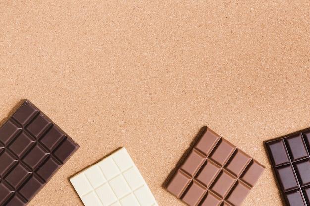 Diferentes tipos de chocolate sobre fondo naranja. Foto gratis