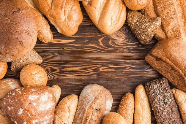 Diferentes tipos de deliciosos panes en el escritorio de madera Foto gratis