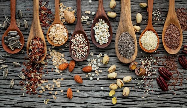Diferentes tipos de granos y cereales sobre fondo de madera en mal estado Foto Premium