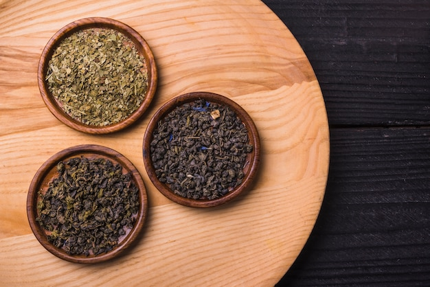 Diferentes tipos de hojas de té secas en mesa de madera Foto gratis