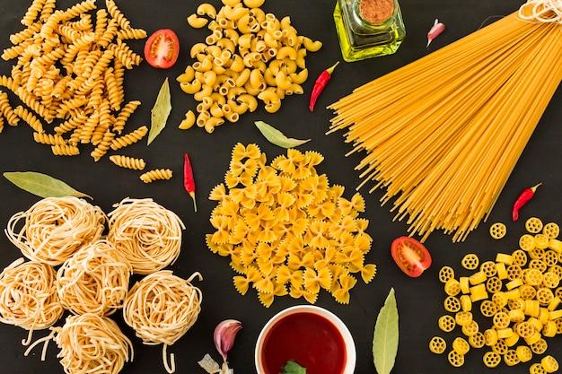 Diferentes tipos de pasta cruda con ingredientes sobre fondo negro Foto gratis