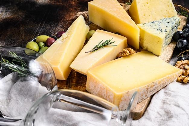 Diferentes tipos de queso, aceitunas y romero. surtido de deliciosos aperitivos. vista superior Foto Premium
