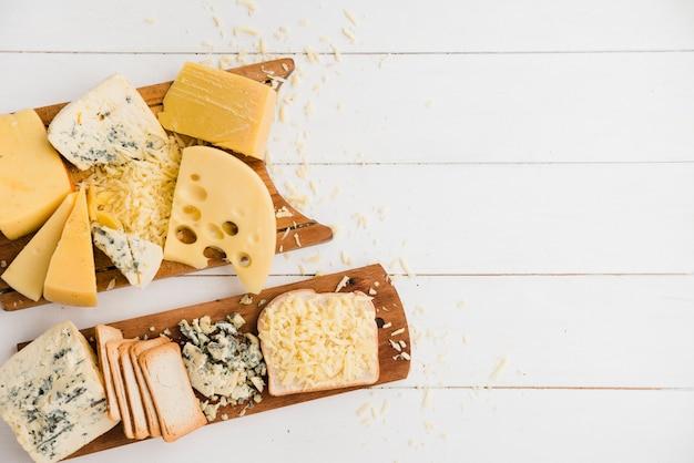 Diferentes tipos de queso con rebanadas de pan en una tabla de cortar sobre un escritorio blanco Foto Premium