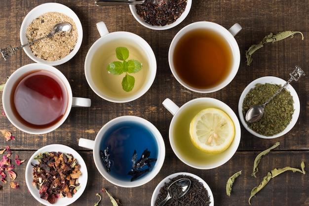 Diferentes tipos de tazas de té de aroma blanco con hierbas en mesa de madera Foto gratis
