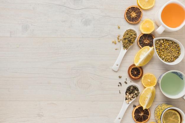 Diferentes tipos de té en taza de cerámica con hierbas y rodajas de pomelo seco en el escritorio Foto gratis