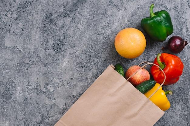 Diferentes tipos de verduras y frutas en el piso gris degradado. Foto gratis