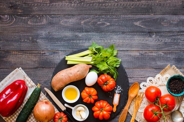 Diferentes tipos de verduras, en una vieja mesa de madera, espacio para texto. Foto Premium