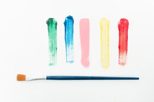 Diferentes trazos de colores junto al pincel. Foto gratis