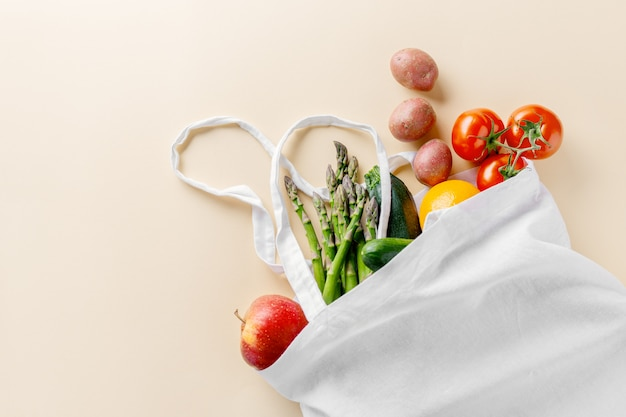Diferentes vegetales en bolsa textil en color beige. Foto gratis