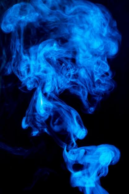 Difunde humo denso de remolino azul sobre fondo negro Foto gratis