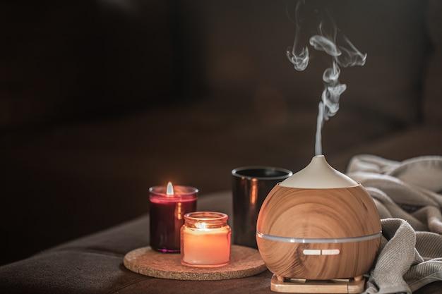 Difusor de aceite en un espacio borroso cerca de velas encendidas. concepto de aromaterapia y salud. Foto gratis