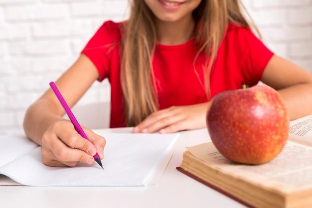 Diligente colegiala escribiendo en el libro de trabajo Foto gratis