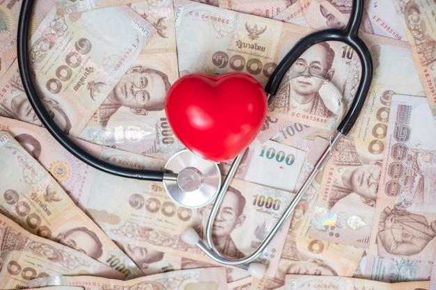 Dinero, forma de corazón rojo y estetoscopio de cardiología Foto Premium