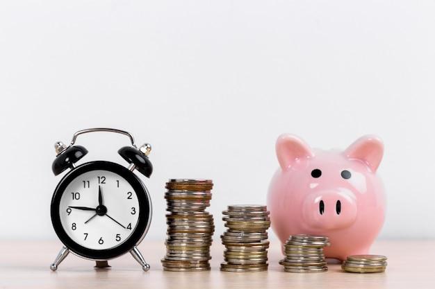Dinero y hucha con pilas de monedas Foto Premium