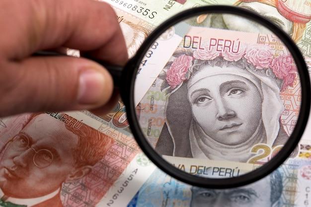 Dinero peruano en una lupa un trasfondo empresarial Foto Premium