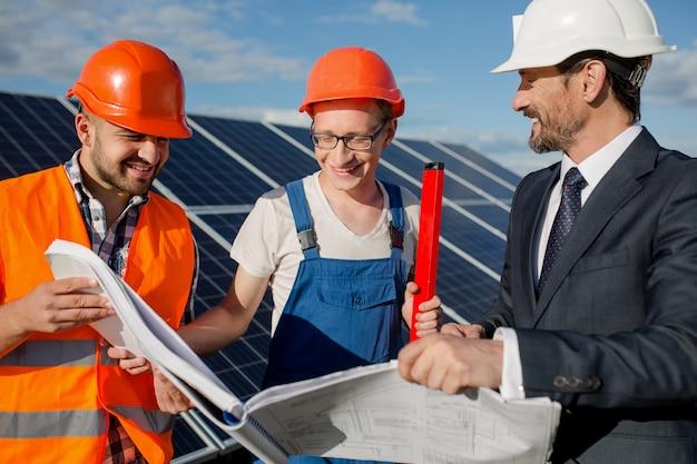 Director, capataz y trabajador mirando en dibujos técnicos a la estación de energía solar. Foto Premium