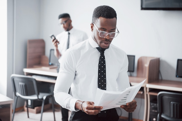 Discutiendo un proyecto. dos hombres de negocios negros en ropa formal discutiendo algo mientras uno de ellos señala un papel Foto Premium